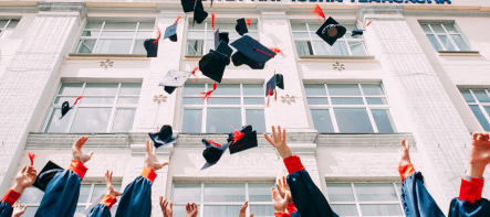 graduation caps being thrown up in the air in front of a buliding
