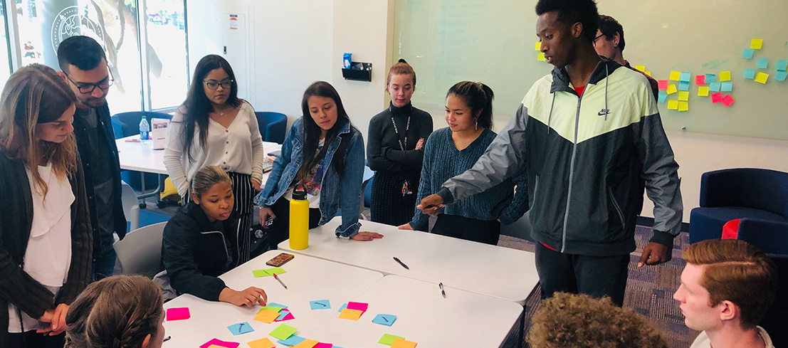 students in designlab using post-it notes to generate ideas